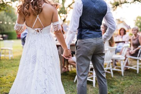 Onherkenbare bruid en bruidegom met gasten bij huwelijksreceptie buiten in de achtertuin. Stockfoto