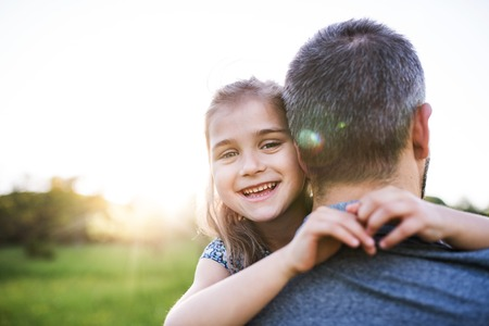 Father holding a small daughter in spring nature at sunset. Banco de Imagens