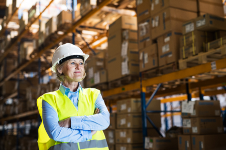 Senior woman manager or supervisor standing in a warehouse, arms crossed.