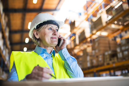 Senior woman warehouse manager or supervisor with smartphone, making phone call.