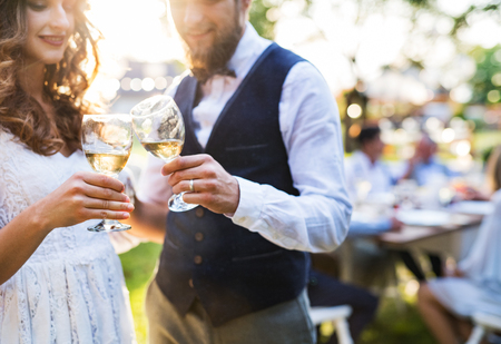 Wedding reception outside in the backyard. Bride and groom clinking glasses with champagne, unrecognizable guests in the background. Stock Photo