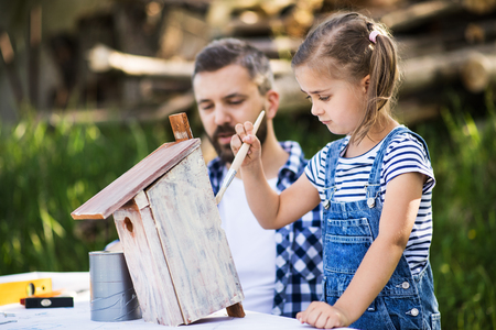Father with a small daughter outside, painting wooden birdhouse. Stock Photo