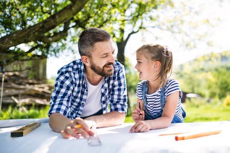 Father with a small daughter outside, planning wooden birdhouse. Stock Photo - 103533582