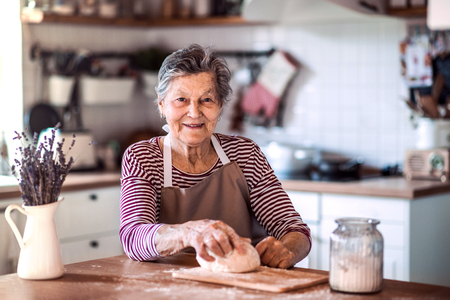 A senior woman kneading dough in the kitchen at home.