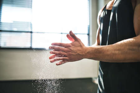 Fit young man in gym smears his hands with magnesium. Close up.