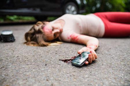 Joven herida con smartphone tirado en la carretera después de un accidente automovilístico, inconsciente. Foto de archivo