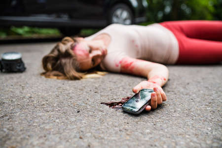 Young injured woman with smartphone lying on the road after a car accident, unconscious. Standard-Bild