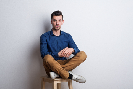Portrait of a young man in a studio sitting on a stool.