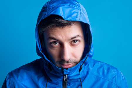 Portrait of a young man in a studio with anorak on a blue background. Stock Photo