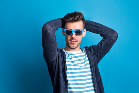 Portrait of a young man in a studio with sunglasses on a blue background.