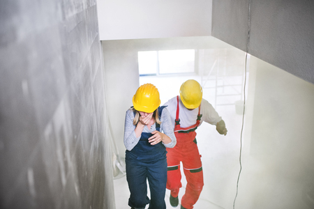 Woman and man workers running up the stairs at the construction site. Stockfoto - 105199705
