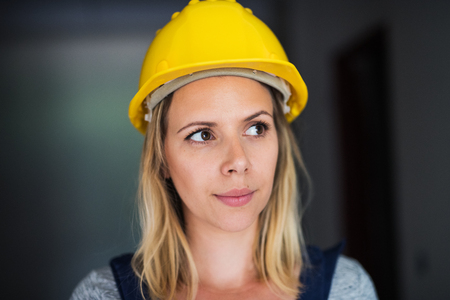 Young woman worker with a yellow helmet on the construction site. Banco de Imagens