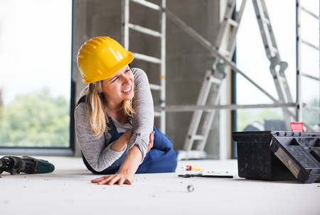 An accident of a woman worker at the construction site. Stock Photo