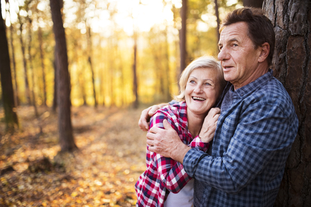 Senior couple on a walk in an autumn forest.