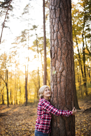 Senior woman on a walk in an autumn forest.