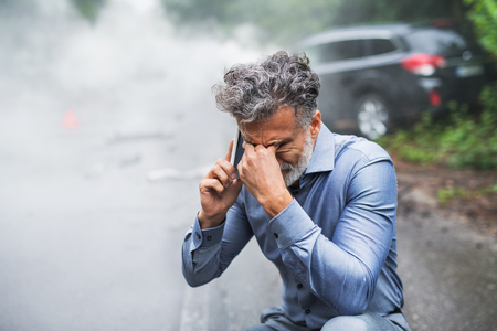 Mature man making a phone call after a car accident, smoke in the background. Archivio Fotografico