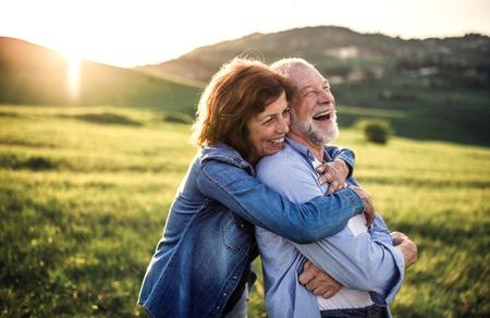 Vue latérale du couple de personnes âgées étreignant à l'extérieur dans la nature printanière au coucher du soleil.