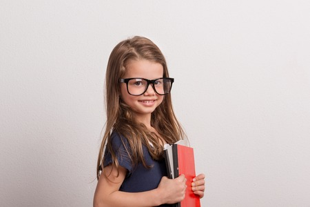 Portrait of a small schoolgirl with big glasses in a studio, holding notebooks. Stock Photo