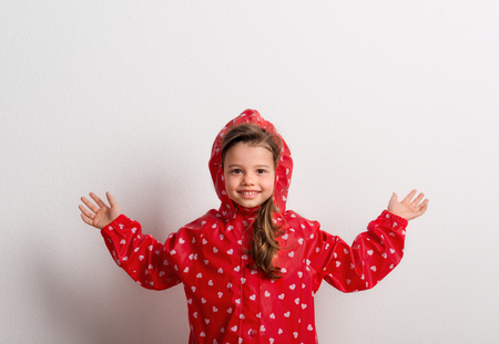 Portrait of a small girl with red anorak in studio on a white background.
