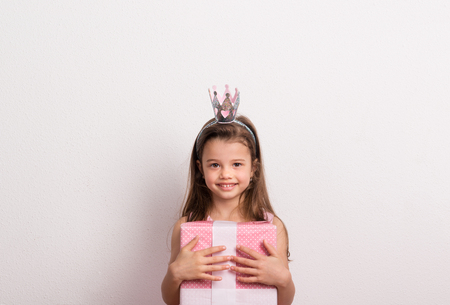 Portrait of a small girl with crown headband in studio, holding a wrapped box. 免版税图像
