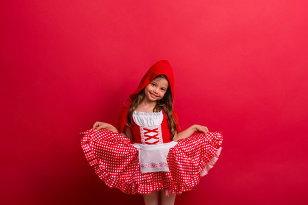 A small girl in Little Red Riding Hood costume in studio on a red background.