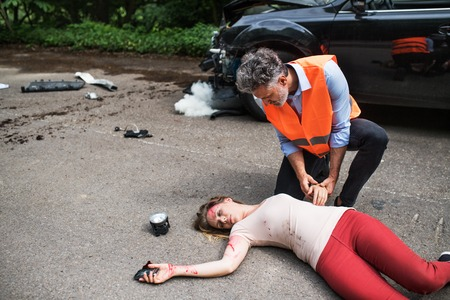 A man helping a young woman lying unconscious on the road after a car accident. Banque d'images