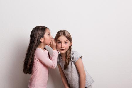 A small girl whispering something in an ear of her friend.