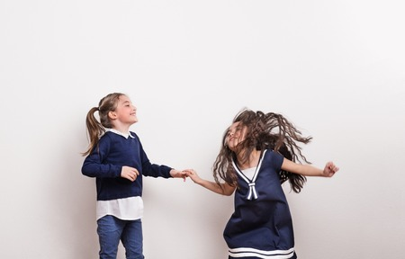Two small girls in a studio, holding hands, having fun.
