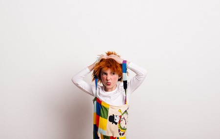A small girl with a wig and a clown costume in a studio, sticking out tongue.