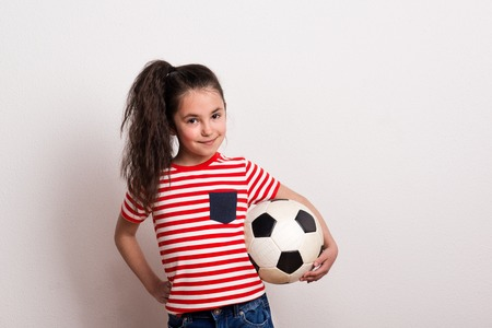 A small girl with a soccer ball and striped T-shirt standing in a studio.