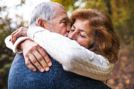 A close-up of a senior couple hugging in an autumn nature, kissing. Foto de archivo