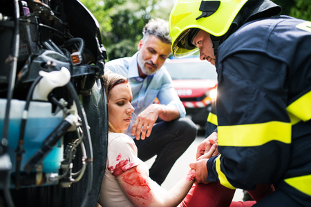 A firefighter helping a young injured woman sitting by the car on a road after an accident.