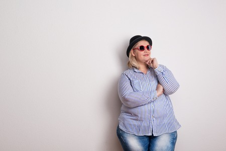Portrait of an attractive voluptuous woman with hat and sunglasses in a studio.