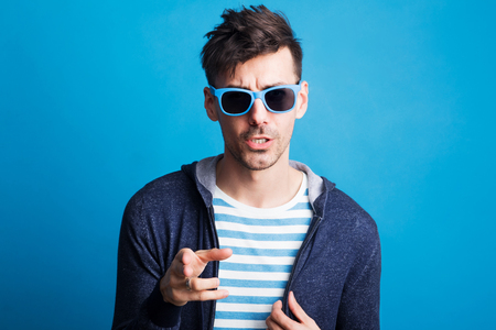 Portrait of a doubtful young man in a studio with hands up.