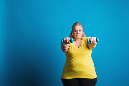 Portrait of an unhappy overweight woman with dumbbells in studio on a blue background. Foto de archivo