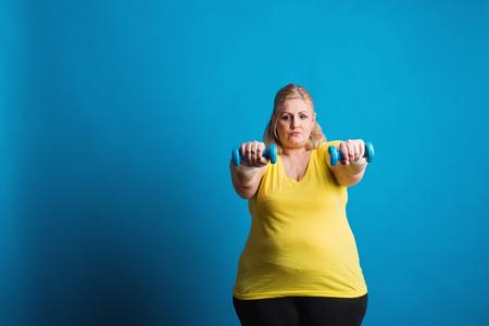 Retrato de una mujer con sobrepeso infeliz con pesas en estudio sobre un fondo azul.