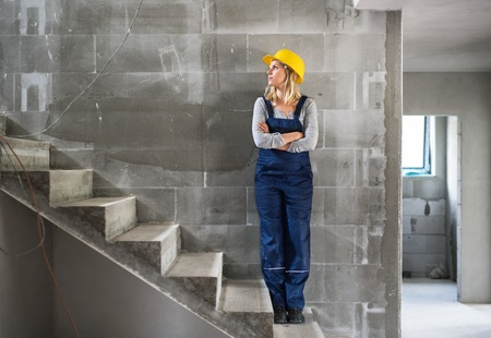 Young woman worker with a yellow helmet on the construction site. Stock Photo