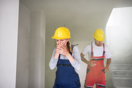 Woman and man workers running from the construction site, coughing. Stockfoto - 107403850
