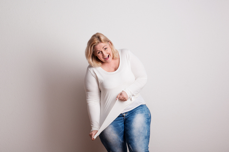 Portrait of an attractive overweight woman in studio on a white background. Foto de archivo