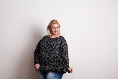 Eine glückliche attraktive übergewichtige Frau im Studio auf einem weißen Hintergrund.