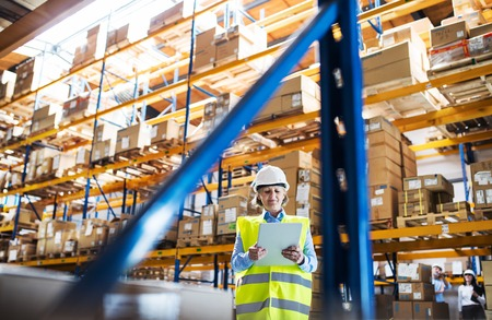 Senior woman warehouse manager or supervisor with tablet, working. Banque d'images