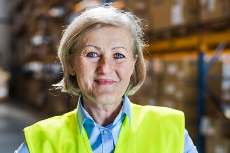 Senior woman manager or supervisor standing in a warehouse.