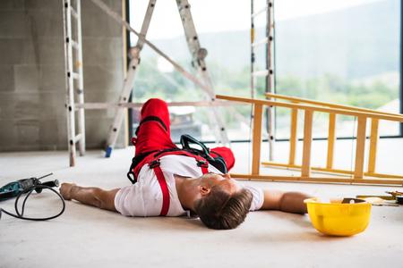 Een mensenarbeider die op de vloer ligt na een ongeval op de bouwplaats.