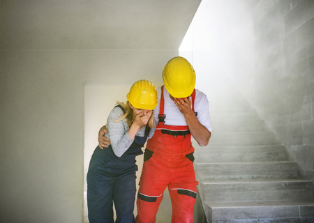 Woman and man workers suffocating at the construction site. Foto de archivo