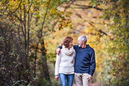 A portrait of a senior couple walking in an autumn nature. Copy space. Reklamní fotografie