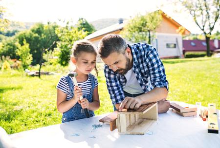 Père avec une petite fille dehors, faisant un nichoir en bois.
