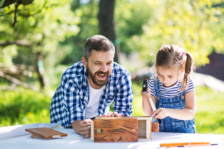 Father with a small daughter outside, making wooden birdhouse. 写真素材
