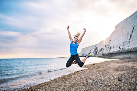Young sporty woman runner in blue sportswear jumping on the beach outside. Stock Photo