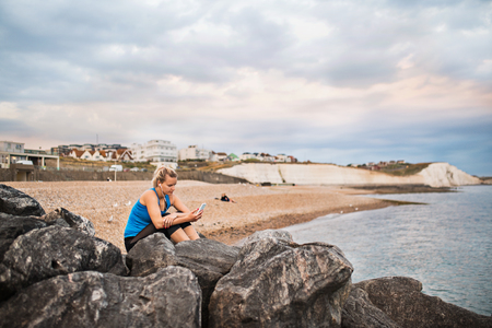 Young sporty woman runner with smartphone sitting on the beach outside, texting. Stock Photo