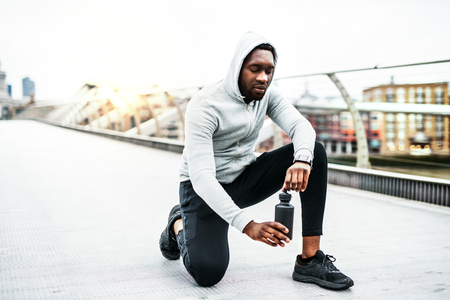 Young sporty black man runner with water bottle on the bridge in a city, resting.